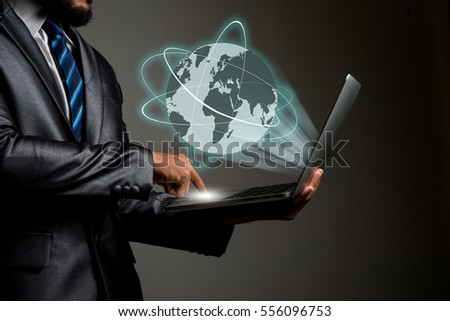 Businessman holding laptop Global erupt from screen, Connecting people network concept.