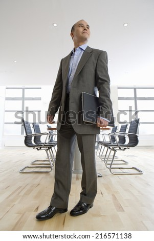 Businessman holding laptop in conference room - stock photo