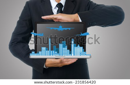 Businessman holding laptop with airplane travel around the city, for business and transport concept. - stock photo