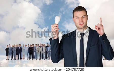 Businessman holding light bulb and pointing against blue sky with white clouds - stock photo