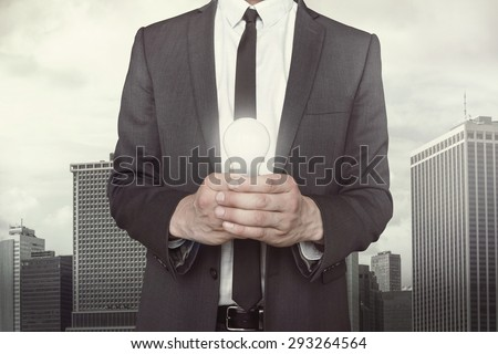 Businessman holding light bulb in hands on cityscape background - stock photo