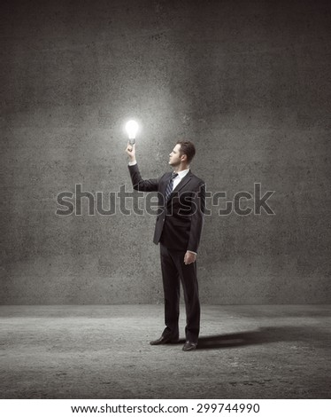 businessman holding lightbulb in gray concrete room - stock photo