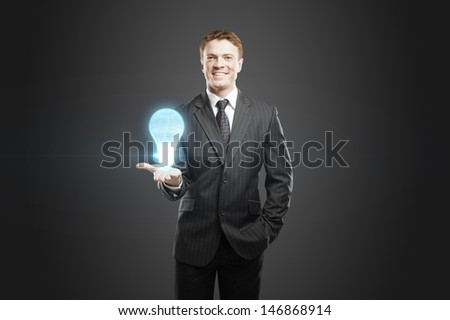 businessman holding lightbulb projection in hand - stock photo