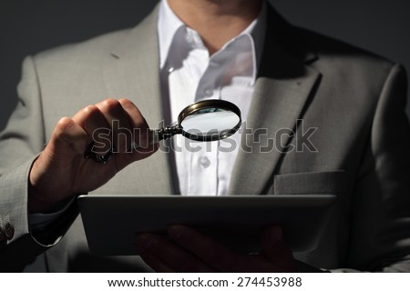 Businessman holding magnifying glass and digital tablet concept for internet search, job search or analysing accounts - stock photo