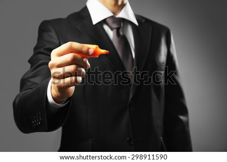 Businessman holding marker on gray background - stock photo