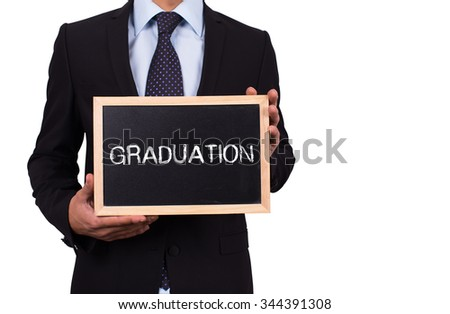 Businessman holding mini blackboard with GRADUATION message - stock photo