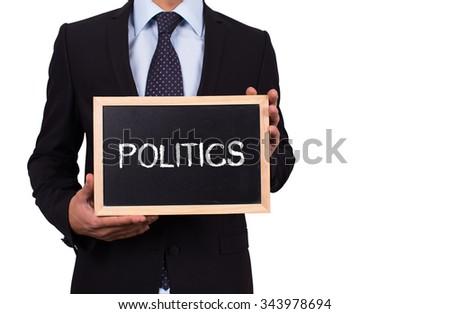 Businessman holding mini blackboard with POLITICS message - stock photo