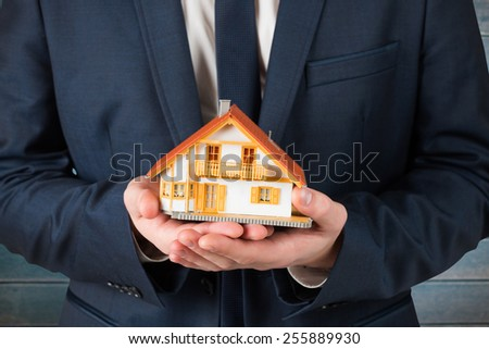 Businessman holding miniature house model against wooden planks - stock photo