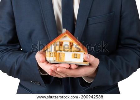 Businessman holding miniature house model on white background - stock photo
