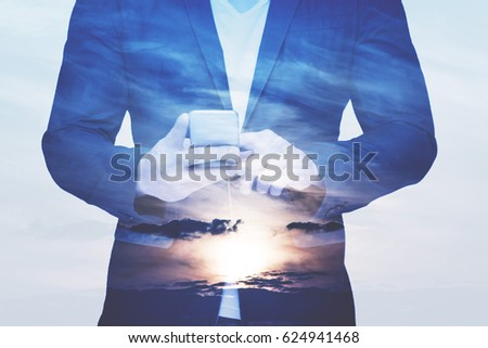 Businessman holding mobile phone. Over gray background
