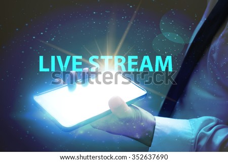 businessman holding mobile phone with LIVE STREAM text on virtual screen. Internet concept. Business concept. Business idea - stock photo