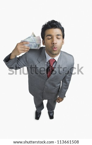 Businessman holding money and puckering - stock photo