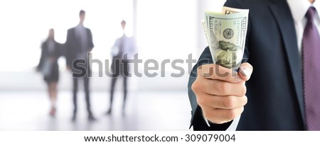 Businessman holding money, United States Dollar (USD) banknotes, in his fist - business and financial panoramic header background - stock photo