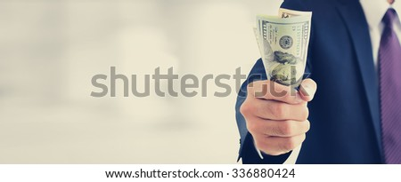 Businessman holding money, united states dollar (USD) bills, on blur white background, vintage tone  - financial and investment panoramic header background concept - stock photo