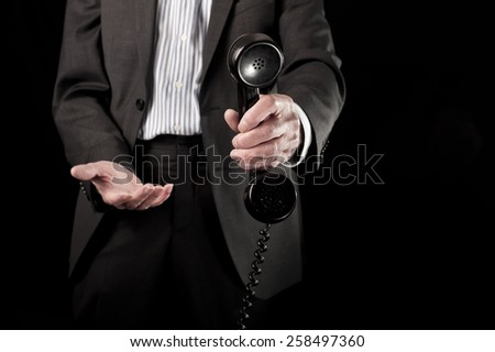 Businessman holding old telephone handset