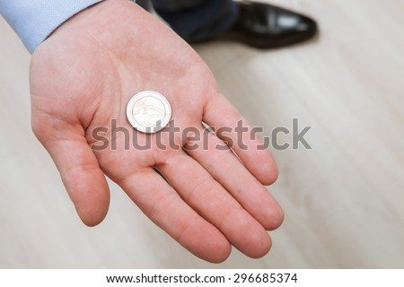 Businessman holding one coin on his palm - stock photo