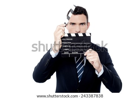 Businessman holding open film slate near his face - stock photo
