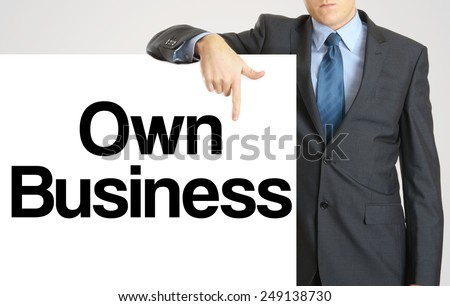 Businessman holding or showing banner with text Own Business - stock photo