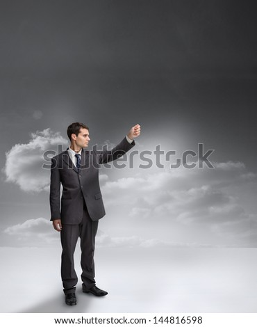 Businessman holding out his arm with clouds on the background