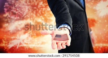 Businessman holding out his hands to the camera against colourful fireworks exploding on black background - stock photo