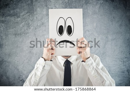 Businessman holding paper with sad face in front of his head. Unhappy businessman, office situation. - stock photo