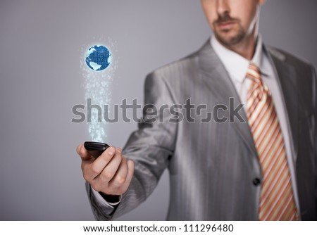Businessman holding phone with 3D projection screen - stock photo