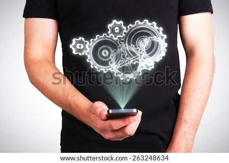 businessman holding phone with gears projection - stock photo