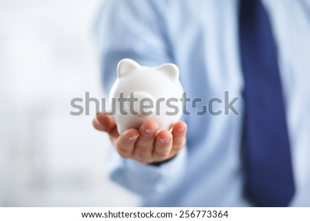 Businessman holding piggy box ,standing in office - stock photo