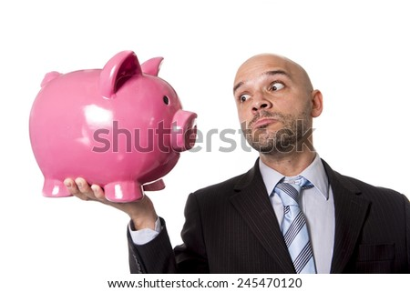 businessman holding piggybank face to face looking the piggy bank in the eye as a you better be full of money warning isolated on white background - stock photo