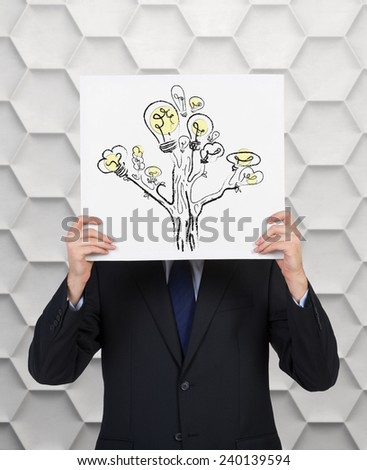 businessman holding poster with lamp tree over head