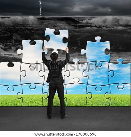 Businessman holding puzzles to assembly change situation from tsunami to beautiful landscape - stock photo
