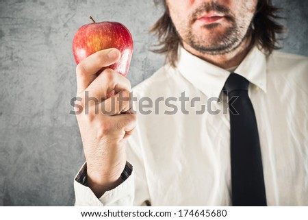 Businessman holding red apple in hand. Healthy eating concept.