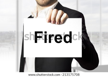 businessman holding sign fired - stock photo