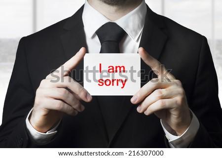 businessman holding sign i am sorry - stock photo