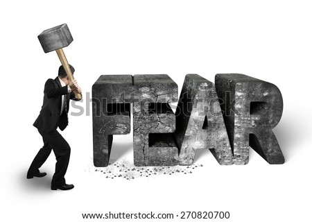 Businessman holding sledgehammer hitting 3d fear mottled concrete word isolated on white background, overcoming fear concept. - stock photo