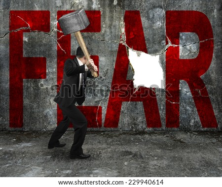 businessman holding sledgehammer hitting red FEAR word on concrete wall with large blank hole, overcoming fear concept. - stock photo