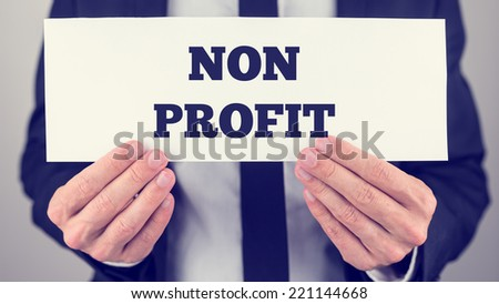 Businessman Holding Small White Signage Showing Non Profit Texts. - stock photo