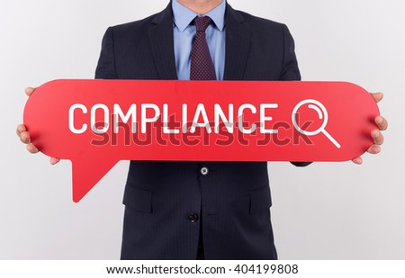 Businessman holding speech bubble with a word COMPLIANCE - stock photo