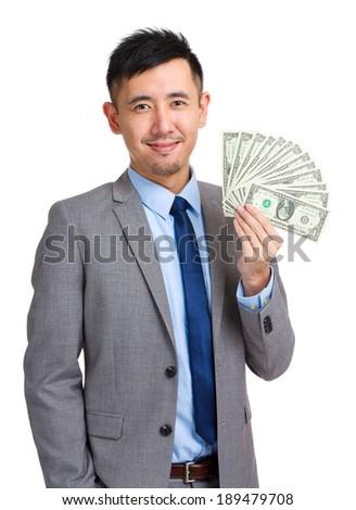 Businessman holding spread of cash - stock photo