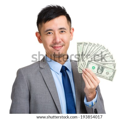 Businessman holding spread of money