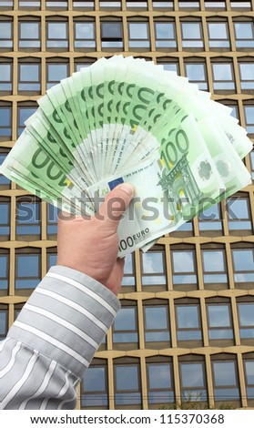 Businessman holding stack banknotes in EUR 100 - stock photo