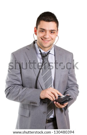 Businessman holding stethoscope to a wallet.