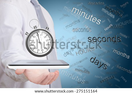 Businessman holding stopwatch on wireless device against a background full of words related to time - stock photo