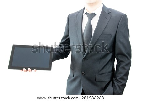 Businessman holding tablet in black suit - stock photo