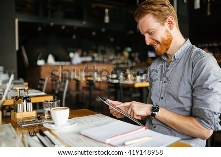 Businessman holding tablet in cafe - stock photo