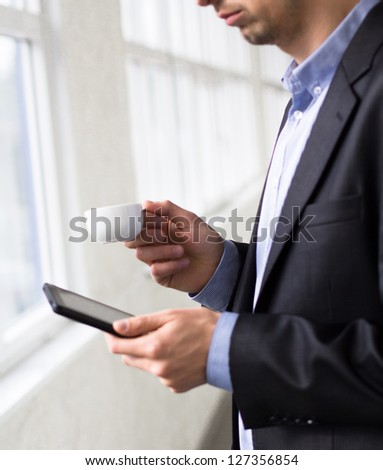 Businessman holding tablet pc and a cup of coffee - stock photo