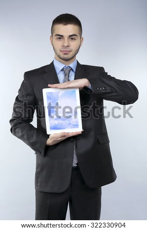 Businessman holding tablet PC with sky in screen. Cloud computing concept - stock photo
