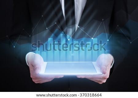 businessman holding tablet with graphs on screen.businessman holding tablet computer with graphs on screen. business concept. technology concept. business concept.  - stock photo