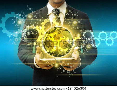 businessman holding tablet world technology social media and cog gear - stock photo