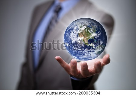 Businessman holding the glowing world in his hands Earth image courtesy of Nasa at http://visibleearth.nasa.gov - stock photo